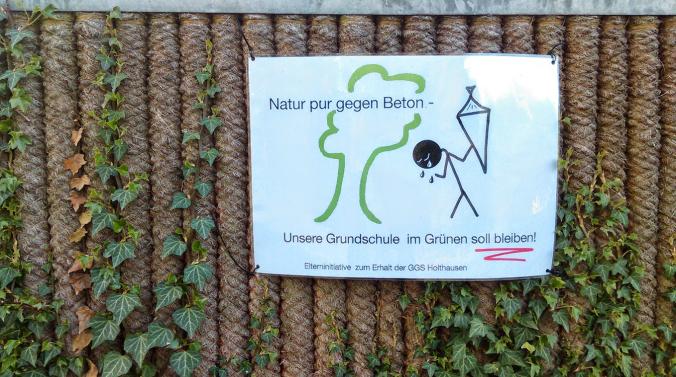 Protestplakate der Elterninitiative zum Erhalt der Grundschule Holthausen am derzeitigen Standort finden sich in ganz Holthausen. Foto: Lars Friedrich